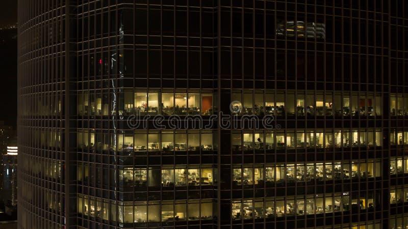 Sluit omhoog voor de gloed van wolkenkrabbervensters bij nacht en mensen binnen, het concept van het nachtleven voorraad Sluit om royalty-vrije stock foto