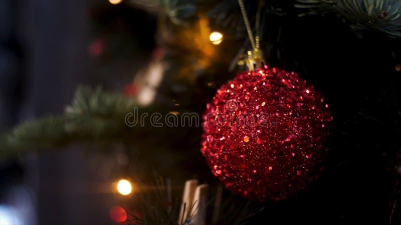Sluit omhoog voor een balstuk speelgoed van rode kleur het hangen op een Kerstboomtak, Vrolijk Kerstmisconcept Voorraadlengte stock foto
