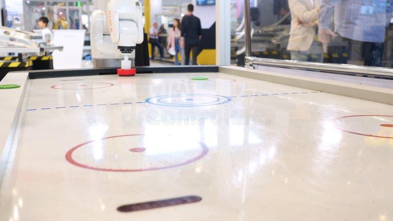 Sluit omhoog voor een striker van de persoonsholding op de lijst van het luchthockey en het spelen met een robot, sportspelen en  royalty-vrije stock afbeelding