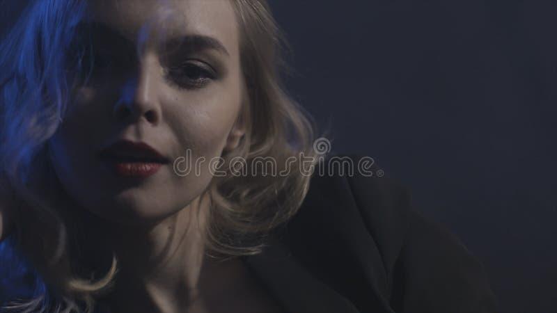 Sluit omhoog voor jonge dame met groene ogen en sensuele lippen op donkere achtergrond, verleidingsconcept actie stock foto