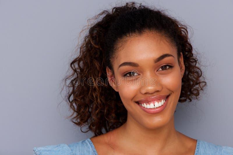 Sluit omhoog vrij het Afrikaanse Amerikaanse meisje glimlachen tegen grijze backgorund stock afbeeldingen