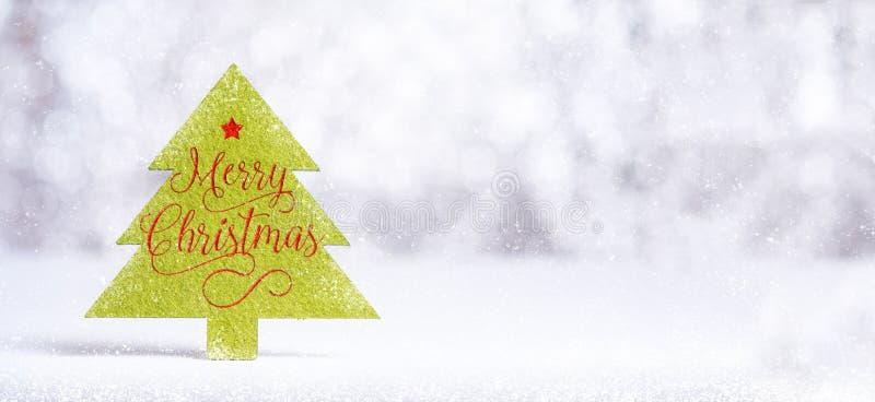 Sluit omhoog Vrolijk Kerstmiswoord op groene Kerstboom met vonk stock foto