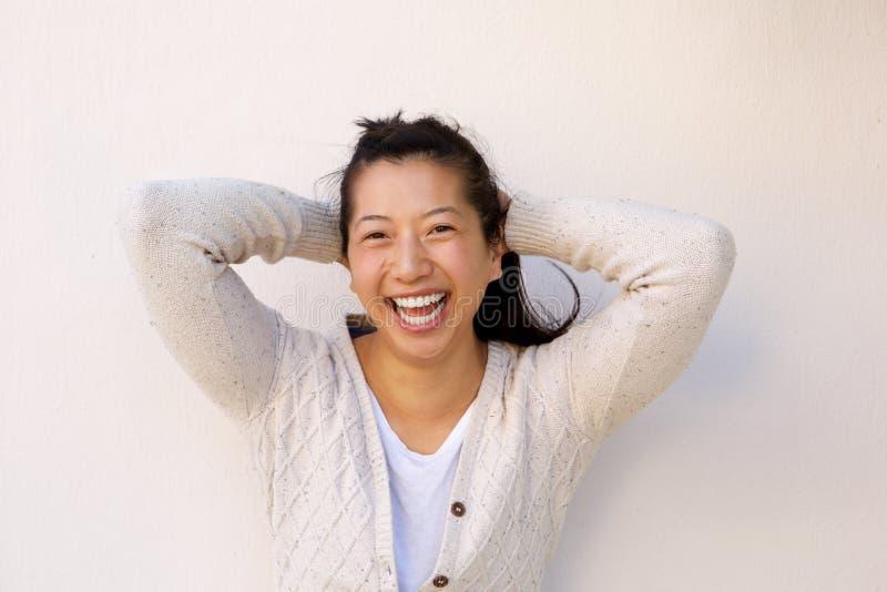 Sluit omhoog vrolijke Aziatische vrouw status met handen achter hoofd royalty-vrije stock afbeelding