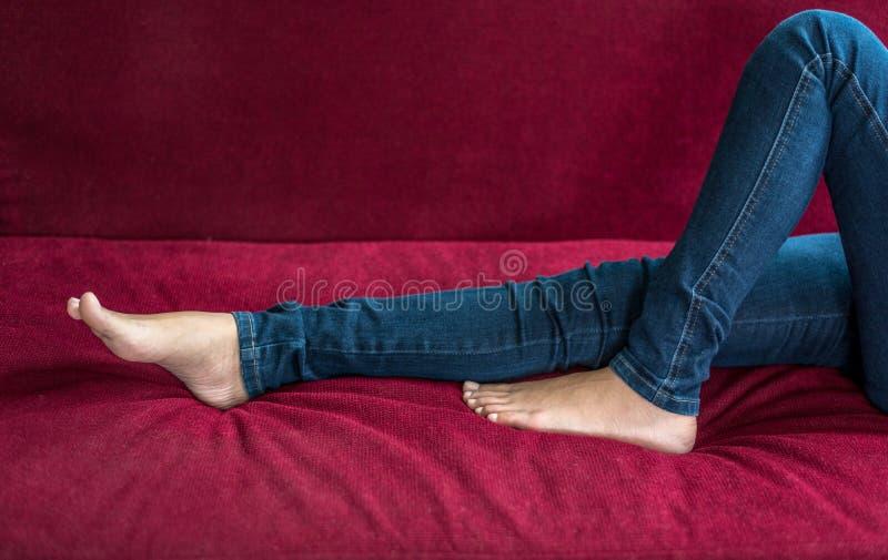 Sluit omhoog vrouw blootvoets en benen die jeansbroek op rode bank dragen thuis als Ontspanning en in vakantie rusten Schoonheid  stock afbeelding