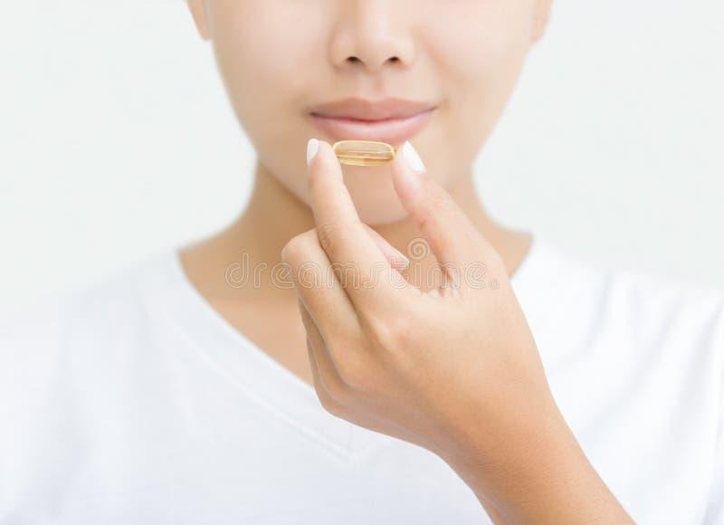 Sluit omhoog vrouw die vitaminecapsule nemen royalty-vrije stock afbeelding