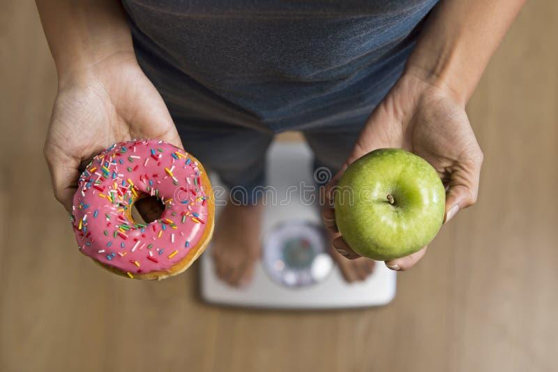 Sluit omhoog vrouw op de holding van de gewichtsschaal in haar fruit van de handappel en doughnut als keus van gezond tegenover o stock fotografie