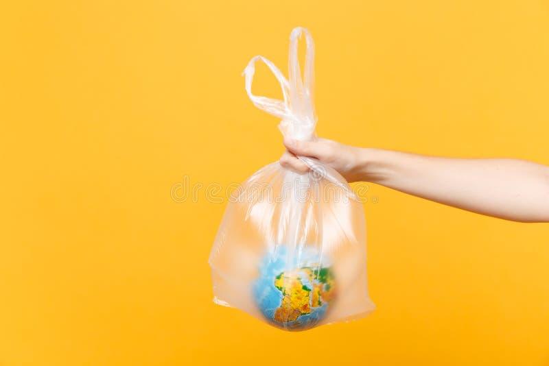Sluit omhoog vrouwelijke greep in de wereldbol van de plastic die zakaarde op gele achtergrond wordt geïsoleerd Het huisvuil van  royalty-vrije stock afbeeldingen