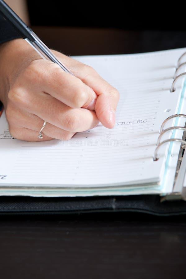 Sluit omhoog Vrouwelijke hand het schrijven nota's stock foto