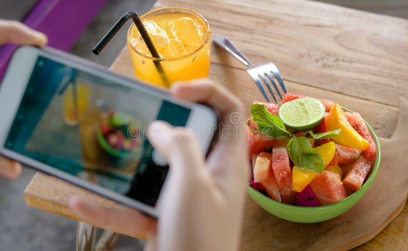 Sluit omhoog vrouwelijke hand met het mobiele telefoonscherm die beeld van fruitsalade en jus d'orange voor het delen van op Inte stock foto's