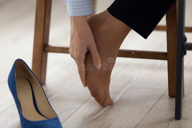 Sluit omhoog vrouwelijke voet masserend om pijn van pijn te verlichten stock afbeelding
