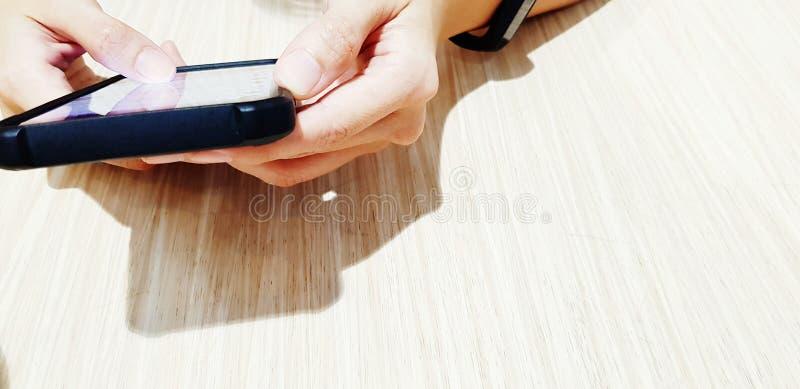 Sluit omhoog vrouwen` s hand gebruikend zwarte smartphone op de houten lijst met exemplaarruimte stock foto's