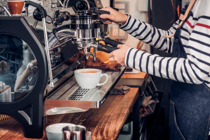 Sluit omhoog vrouwenbarista makend hete koffie met machine bij teller stock afbeeldingen