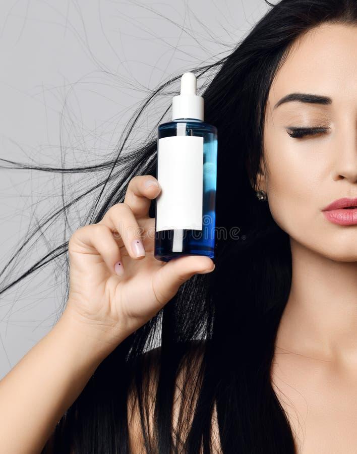 Sluit omhoog vrouwenbrunette met lang haar die in de wind en de gesloten ogen fladderen die een fles op grijs tonen Reclameconcep royalty-vrije stock foto