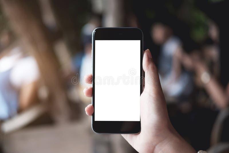 Sluit omhoog Vrouwenhand Gebruikend een Slimme Telefoon bij de winkel van de koffiekoffie met royalty-vrije stock afbeelding