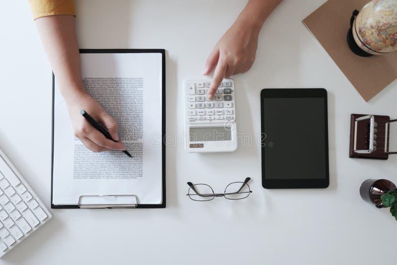 Sluit omhoog vrouwenhand terwijl het gebruiken van calculator in bureau, hoogste mening, model stock foto