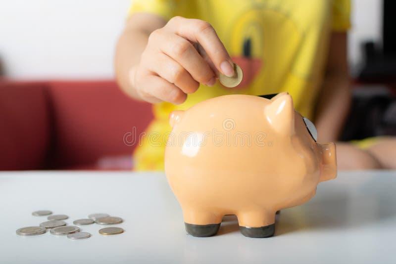 Sluit omhoog vrouwenhand zettend muntstukken in spaarvarken stock afbeelding