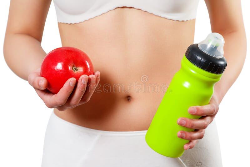 Sluit omhoog vrouwenmaag met handen houdend water en Reg. appel op wit wordt geïsoleerd dat stock foto
