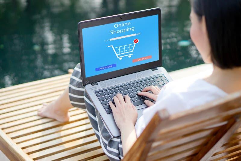 Sluit omhoog vrouwenzitting en online winkelend op laptop computer voeg binnen aan karfunctie toe stock afbeeldingen