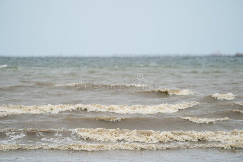 Sluit omhoog vuile bruine golf van het overzees aan het strand stock afbeelding