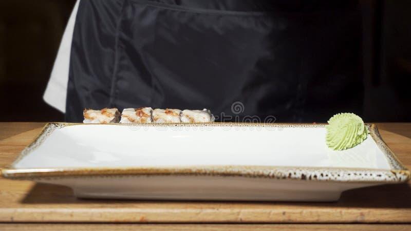 Sluit omhoog want de chef-kok zwarte kokende handschoenen drukkend groene wasabisaus op een plaat voor voorbereide broodjes indie royalty-vrije stock foto