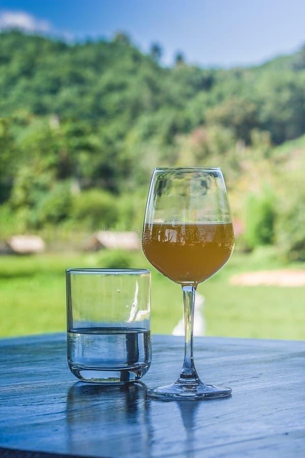 Sluit omhoog water en jus d'orange in glas op houten lijst royalty-vrije stock foto