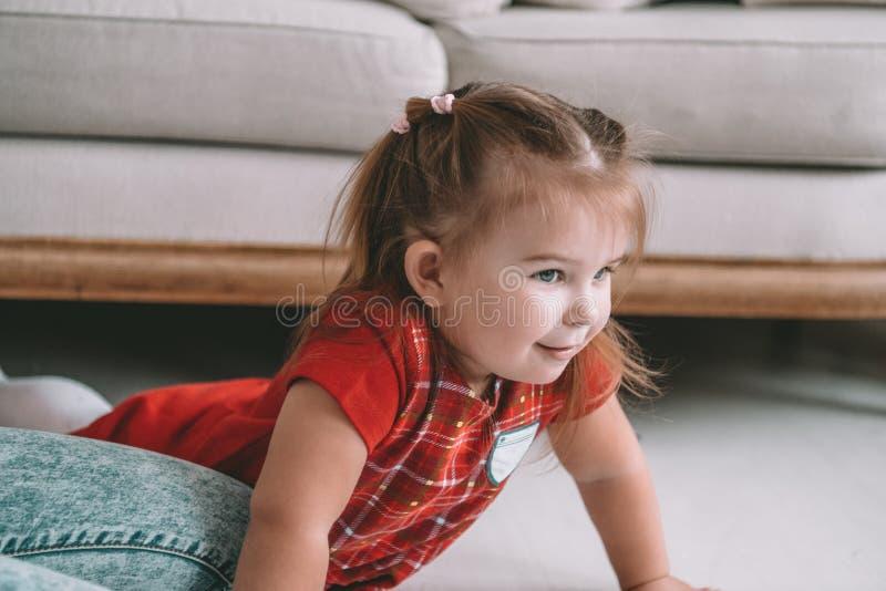 Sluit omhoog weinig het aanbiddelijke nadenkende meisje dromen liggend op een vloer in een woonkamer bij modern huis stock afbeelding