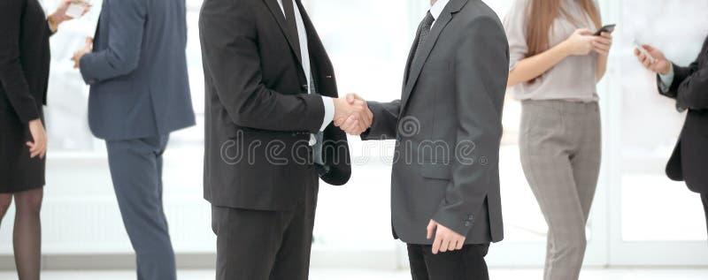 Sluit omhoog welkom handdruk van bedrijfsmensen in het bureau royalty-vrije stock afbeelding
