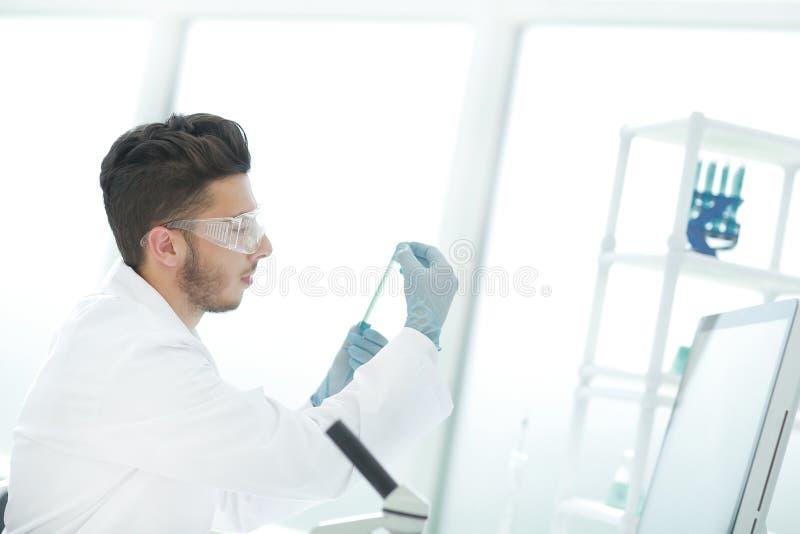 Sluit omhoog wetenschapper met een medische buis die zich in het laboratorium bevinden stock afbeeldingen
