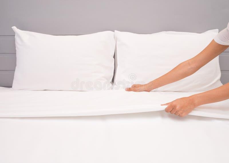 Sluit omhoog wit het bedblad van de handopstelling in hotelruimte stock foto's