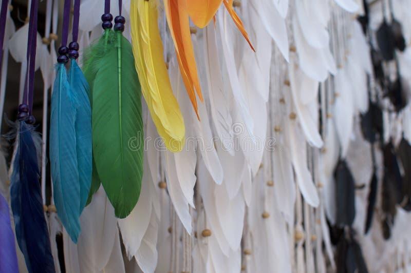 Sluit omhoog witte en gekleurde veren van een dreamcatcher die in Ubud Art Market hangen royalty-vrije stock afbeelding
