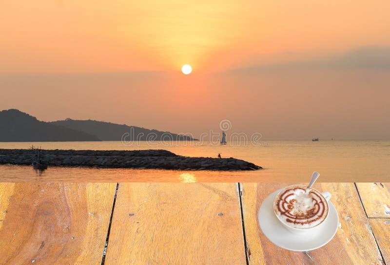 Sluit omhoog witte koffiekop op houten lijst en mening van zonsondergang of zonsopgangachtergrond stock foto