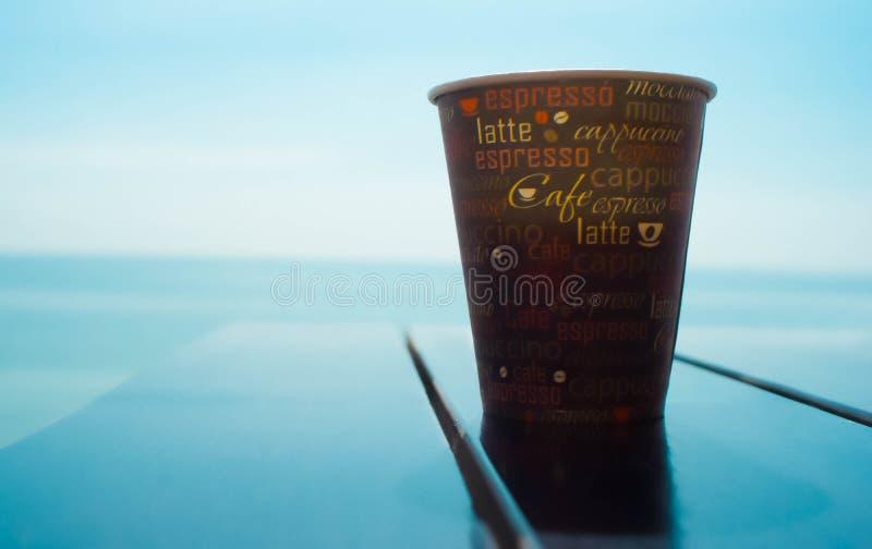 Sluit omhoog witte koffiekop op houten lijst en mening van zonsondergang of zonsopgangachtergrond stock afbeeldingen
