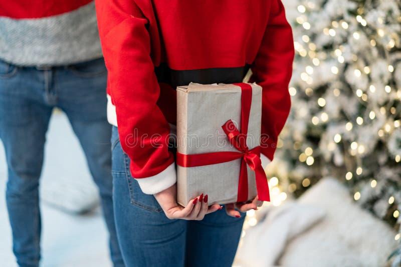 Sluit omhoog, wordt het meisje in santasweater bereid om een gift te geven en de kerel wacht royalty-vrije stock afbeelding