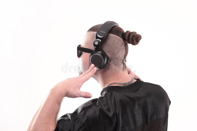 Sluit omhoog Zachte nadruk de rapper kerel in de hoofdtelefoons bekijkt een exemplaar van de ruimte stock foto