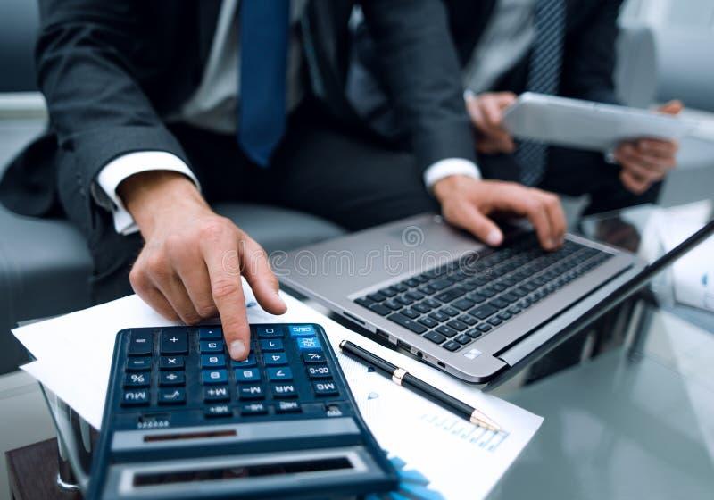Sluit omhoog zakenman die een calculator voor het berekenen van financiële winst gebruiken royalty-vrije stock foto's