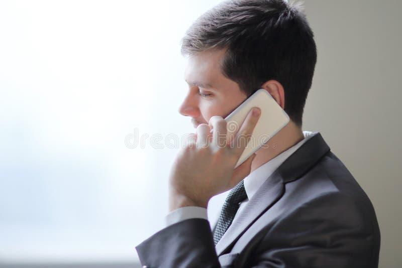 Sluit omhoog zakenman die op smartphone spreken terwijl status dichtbij een bureauvenster royalty-vrije stock foto's