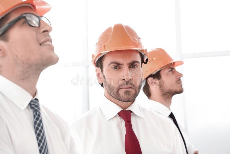 Sluit omhoog zakenman en een groep architecten die zich verenigen stock afbeelding