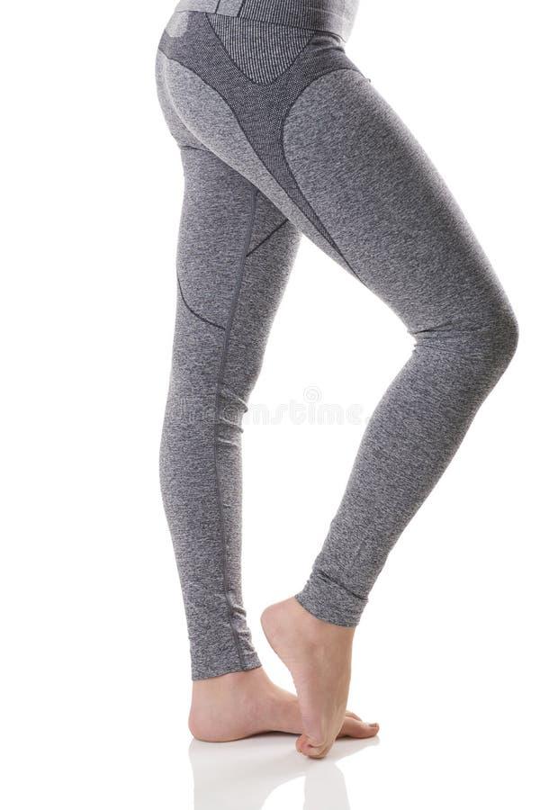 Sluit omhoog zijaanzicht die van vrouwenbenen de spieren van de voet in grijs sporten thermisch ondergoed uitrekken met patroon stock fotografie