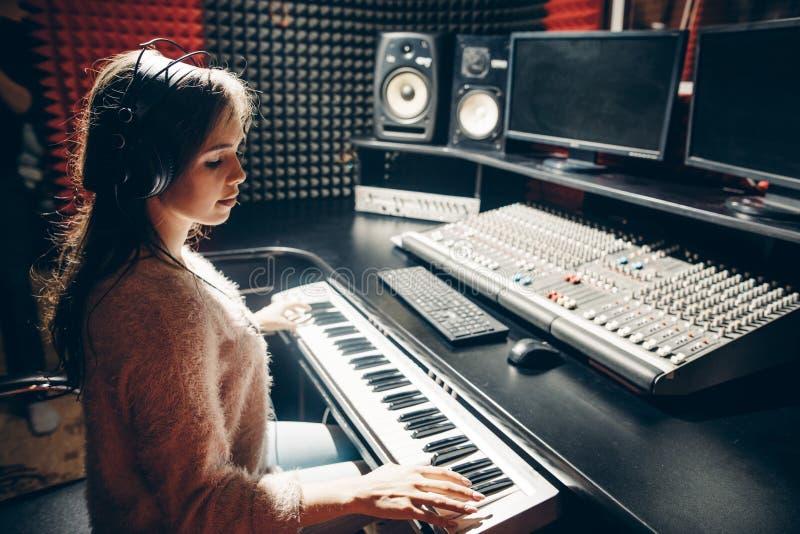 Sluit omhoog zijaanzichtfoto het begaafde mooie meisje plaing op de synthesizer stock afbeeldingen