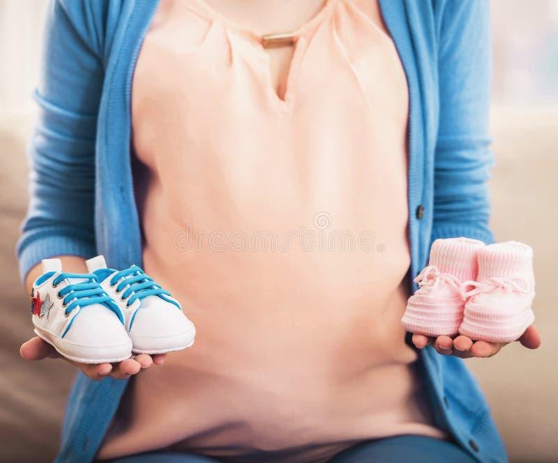 Sluit omhoog Zwangere Jonge Vrouw met Kleine Laarzen royalty-vrije stock afbeelding