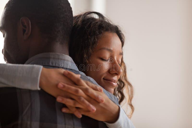 Sluit omhoog zwarte Afrikaanse vrouw omhelzend echtgenoot royalty-vrije stock fotografie