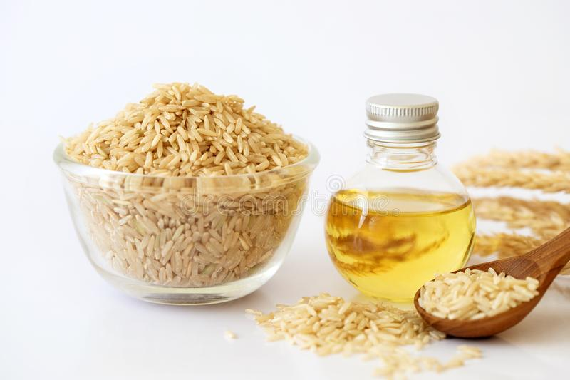 Sluit ongepelde rijstzaad en omhoog de olie van rijstzemelen in fles en unmilled rijst op witte achtergrond, goede vetten voor ge stock foto