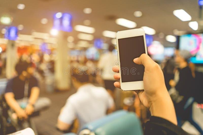 Sluit op slimme telefoon in vrouwenhand en vaag beeld van omhoog mensen stock afbeelding