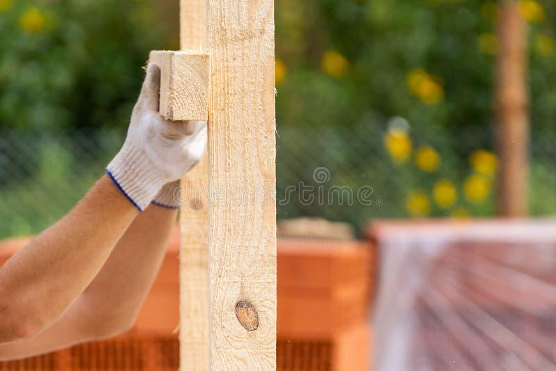 Sluit opgedoken foto van arbeiders indienen witte beschermende handschoenen houdend plankraad die het installeren op speciale hui stock afbeeldingen