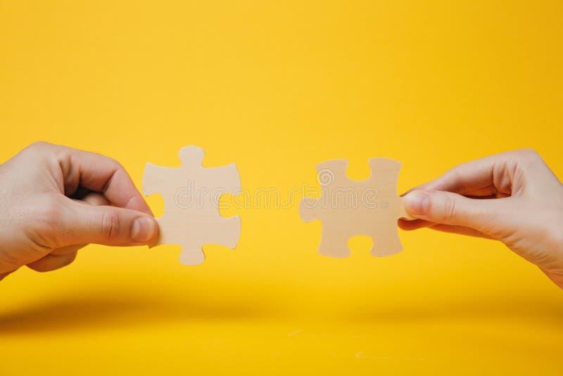 Sluit opgedoken foto van handen houdend het proberen om stukken van de paar de houten puzzel op heldere geel te verbinden royalty-vrije stock afbeeldingen