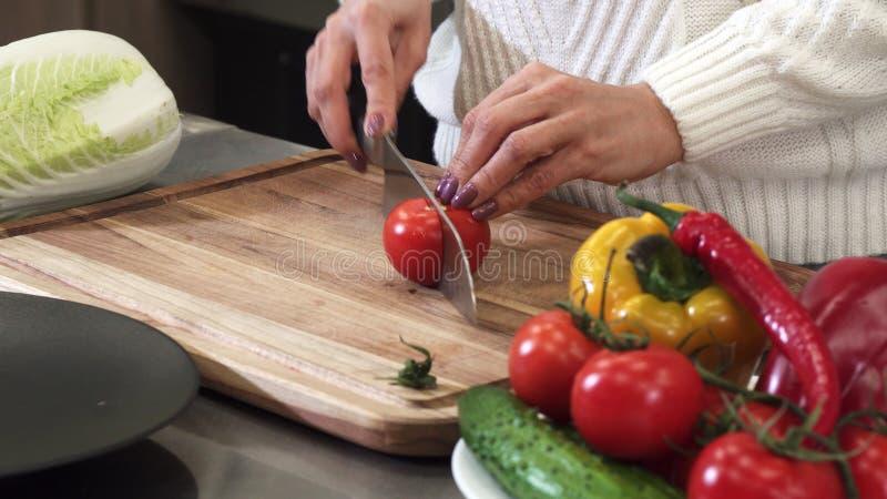 Sluit opgedoken schot van een vrouwen snijdende tomaat op een houten scherpe raad stock afbeeldingen