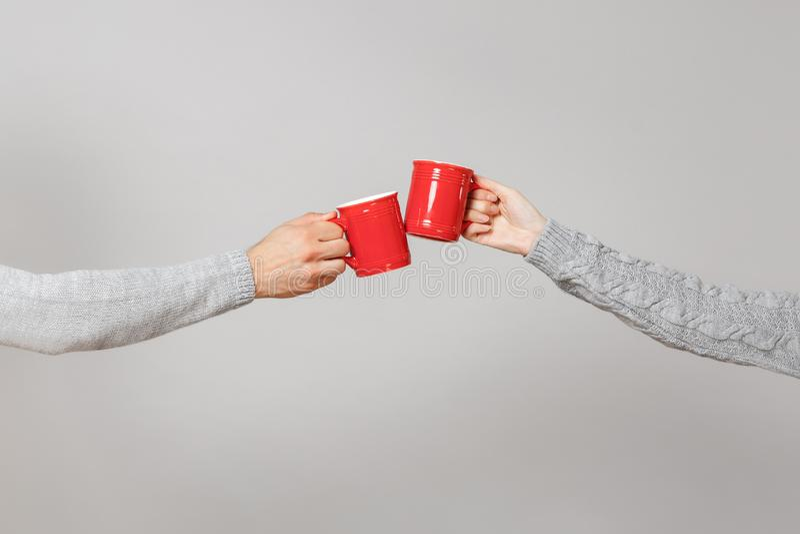 Sluit opgedoken van vrouw, man twee rode kop theeën van de handen de horizontale holding, clinking geïsoleerd op grijze muurachte royalty-vrije stock foto