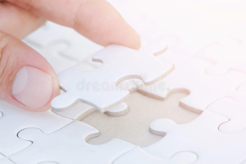 Sluit palmhand plaatste omhoog een laatste stuk van de onvolledige witte puzzel aan de opdracht volledig te maken eindigen, stock afbeelding