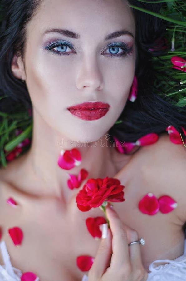 Sluit portret die van donkerbruine vrouw op gras met rode lippen omhoog liggen en uitgestrooid met roze bloemblaadjes Schoonheid, stock afbeelding
