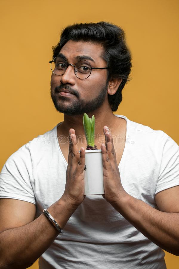 Sluit portret die van knappe Indische kerel bloem omhoog behandelen stock fotografie